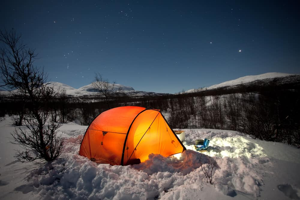 This is an illuminated tent during nighttime at a snowy winter camp site.