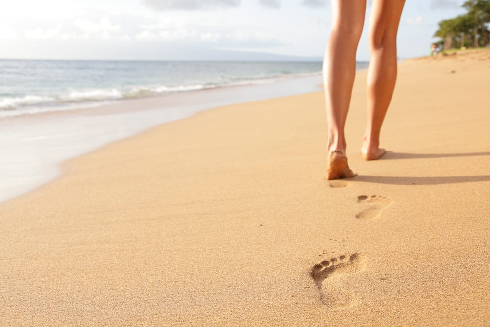 Woman walking by the beach leaving footprints on the sand.