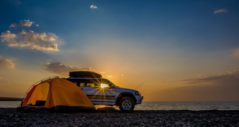 Camper van and tent near the lake during sunrise.