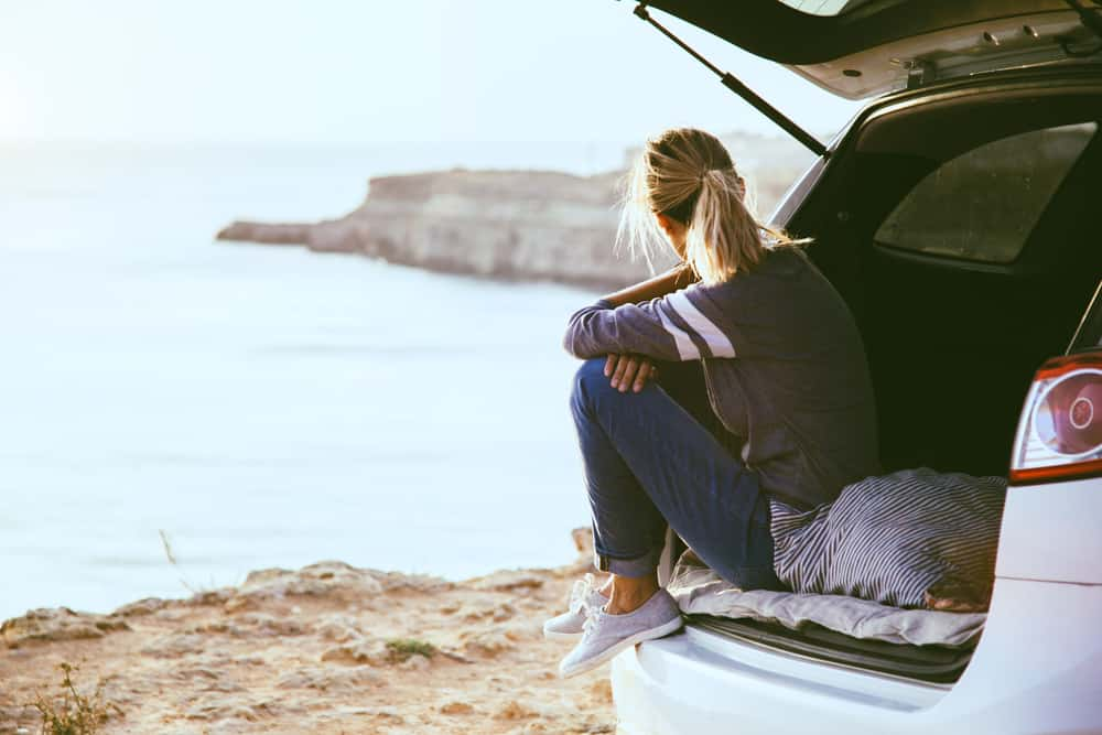 Woman relaxing inside car trunk and looking out the sea.