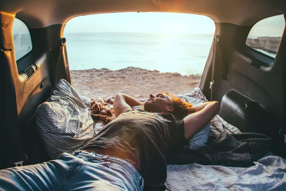 Man sleeping inside car trunk.