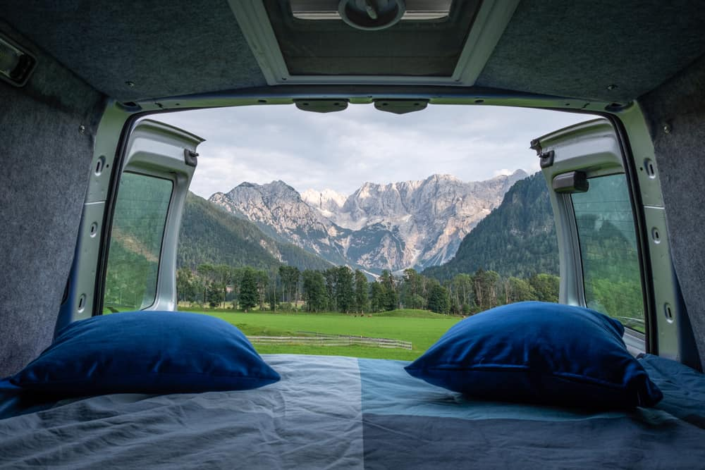 View of the green meadow from the bed in camper van.