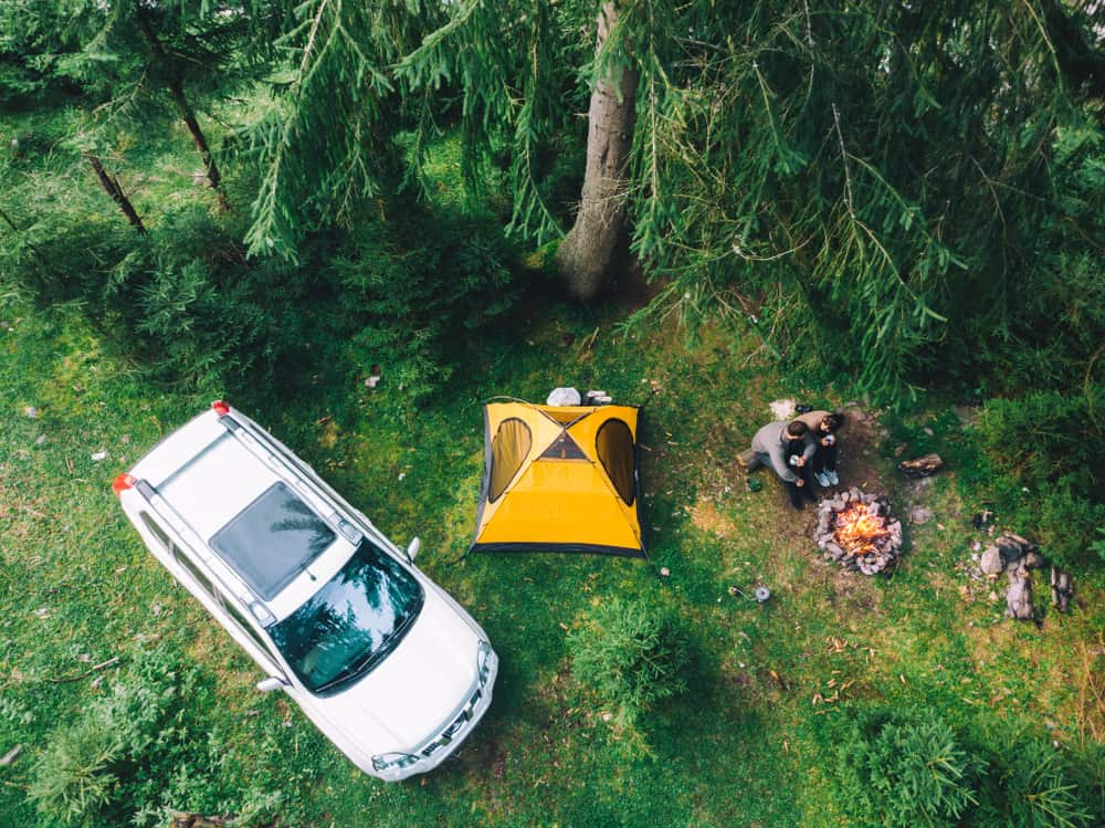 Aerial view of couple drinking tea near campfire.