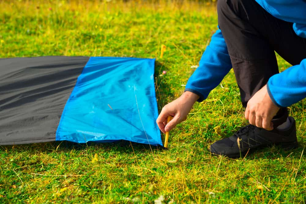 A close look at a man installing footprint for the tent.