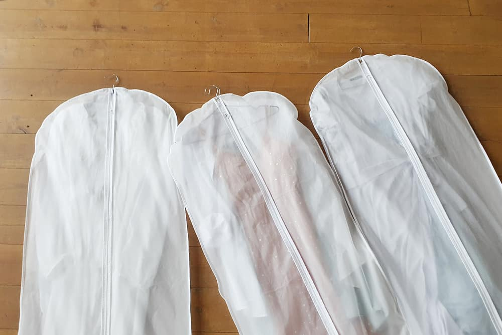 Three garment bags on the wooden floor.
