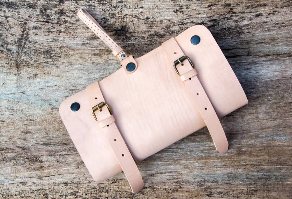 This is a close look at a pink dopp kit with leather straps.