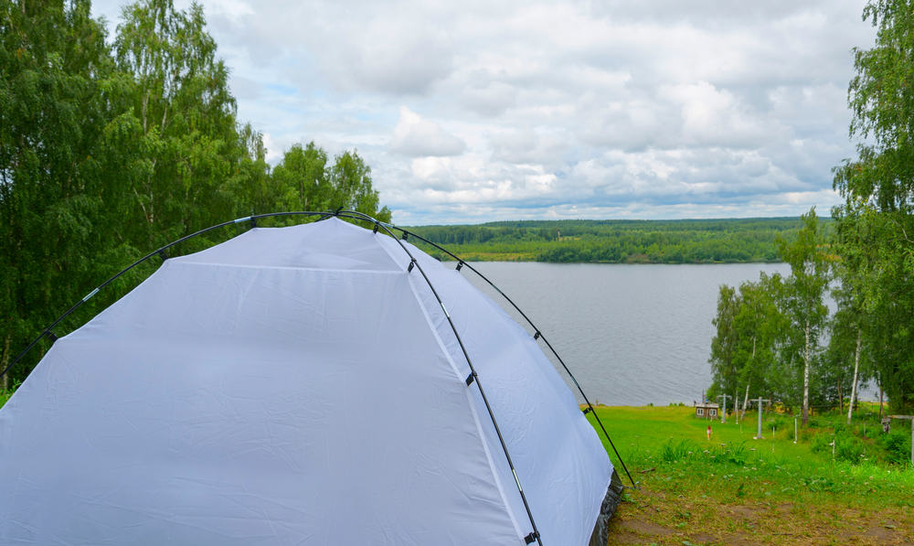 A bright white tent setup by the river.