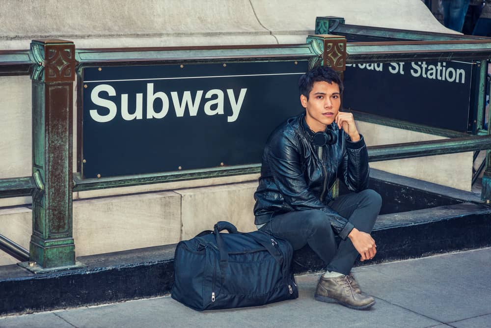A man with a black duffel bag by the subway entrance.