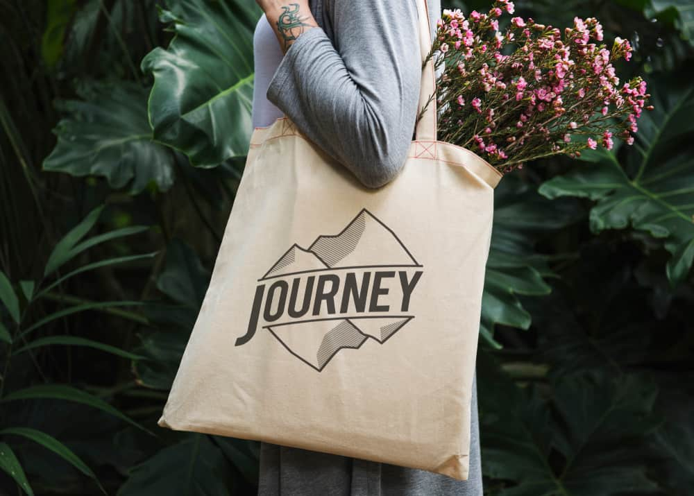 A woman carrying a travel tote with journey written on it.