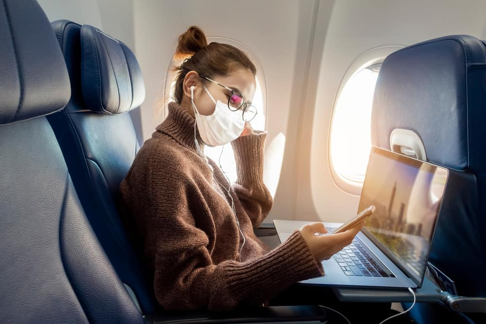Woman in an airplane wearing face mask.