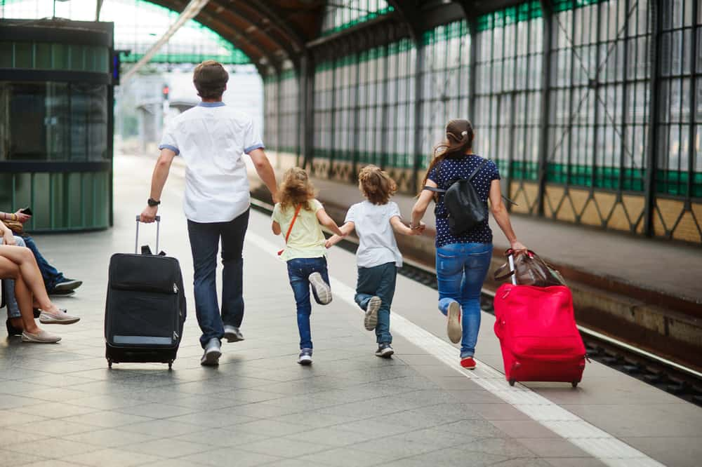 Family of four rushes on platform of railway train station.