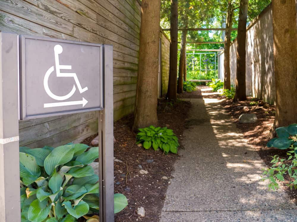 Concrete trail in the park with ADA Compliant Handicap disability sign.