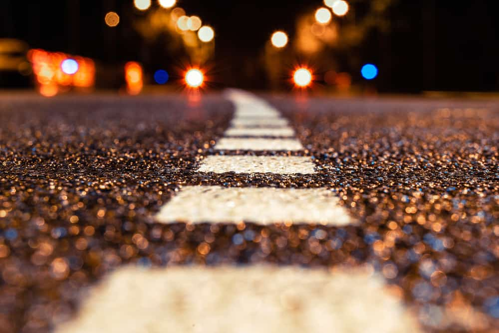 Macro shot of an asphalt road during night with city lights.