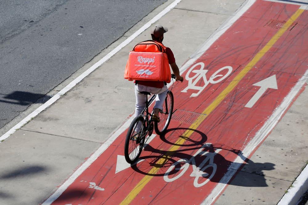 A delivery boy on a bike lane riding his bike.
