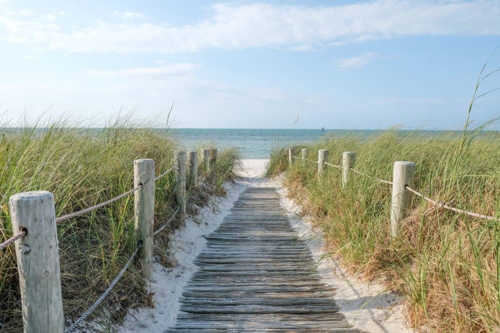 A boardwalk framed with rope railings leading to the beach.