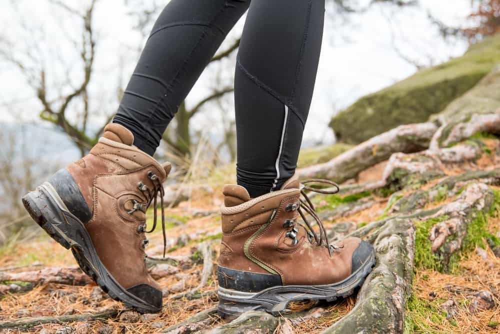 Woman in boots hiking on a root terrain.