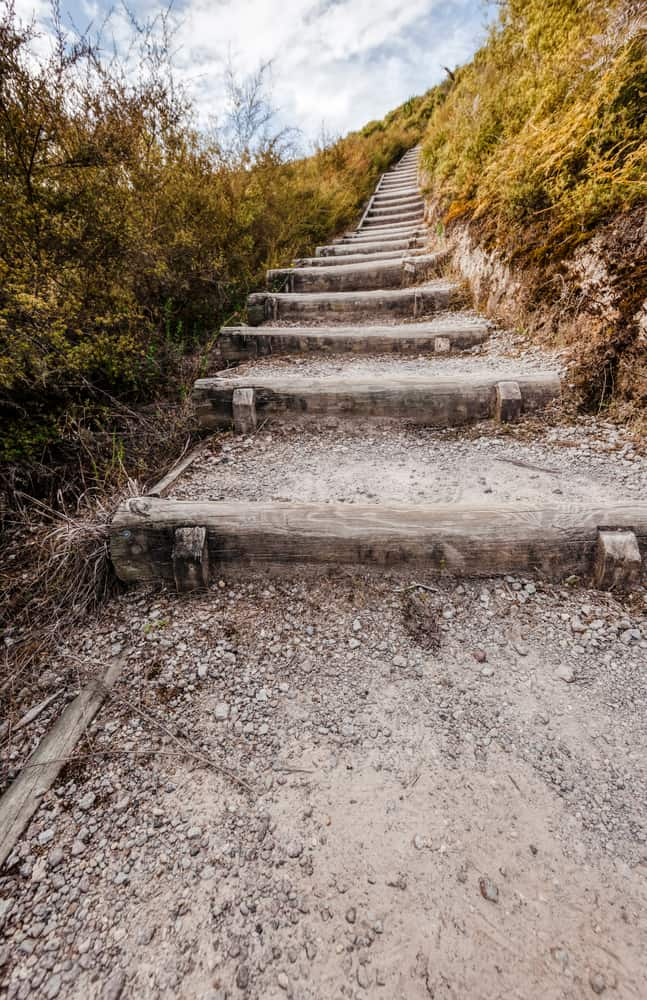 A hiking trail uphill in volcanic landscape with wooden steps.