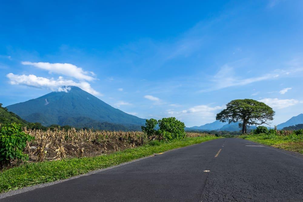 Asphalt road at Guatemalan Boca Costa with serene volcanic landscape.