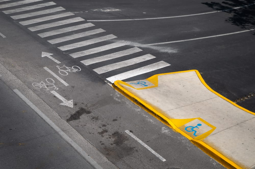 Road with traffic lines, bike lane, and a ramp for the disabled.