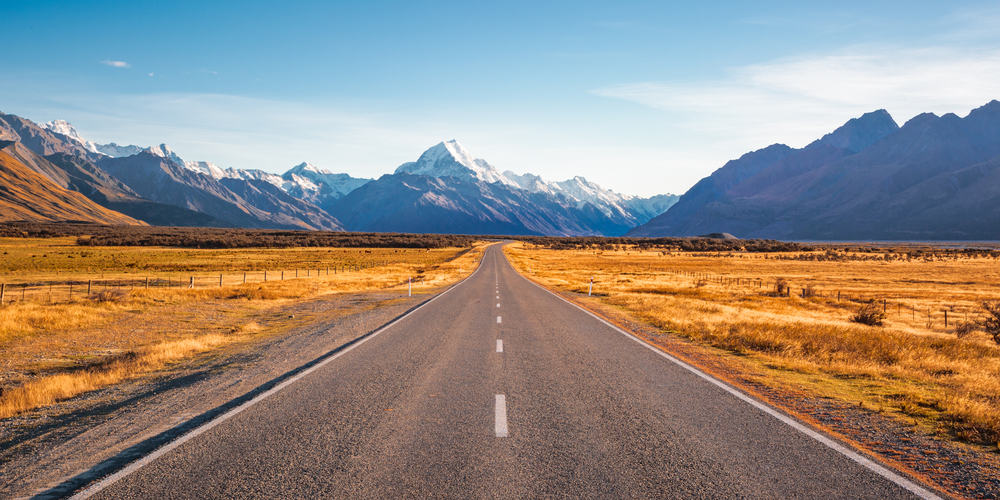 A long, straight road leading towards a snow capped mountain in New Zealand.