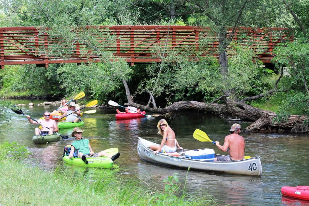Adults in colorful canoes and kayaks paddling on the Huron River Water Trail.